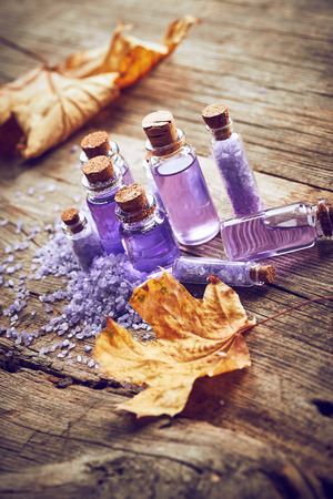 spa still life: Purple Spa still life with autumn leaves on wooden background Stock Photo