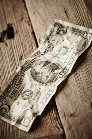 five dollars: Five dollars on wooden background Stock Photo