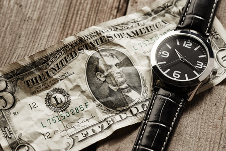 five dollars: Five dollars and clock on wooden background Stock Photo