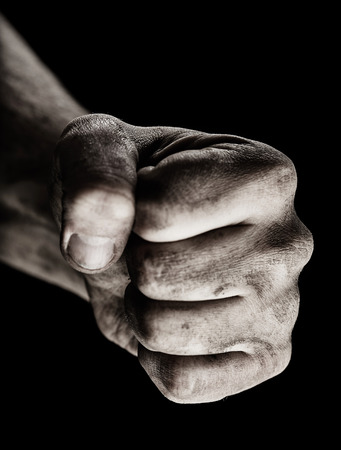 Male clenched fist on black background