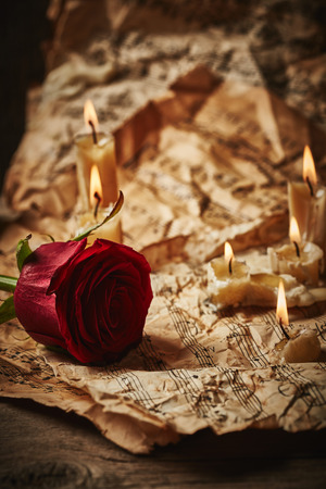 octaves: Vintage music sheets with red rose and candles on wooden background