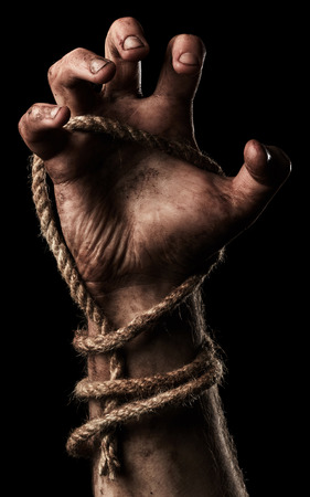 fist clenched: Male hand with rope on black background. Conception aggression