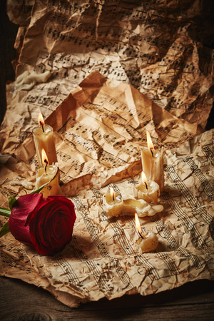 Vintage music sheets with red rose and candles on wooden background photo
