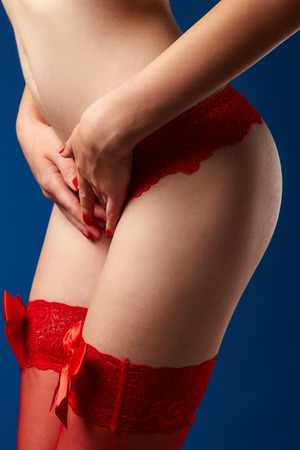 Female body in red lace underwear on blue background