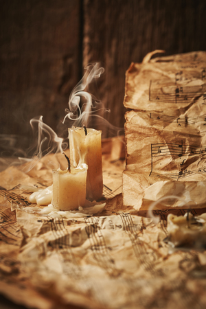 octaves: Vintage music sheets with candles on wooden background