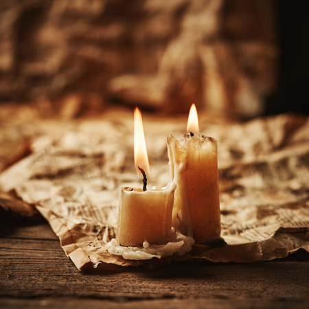 music symbols: Vintage music sheets with candle on wooden background Stock Photo