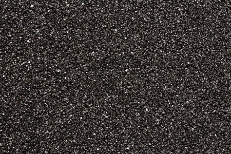 Abstract black stones background. Black sand texture