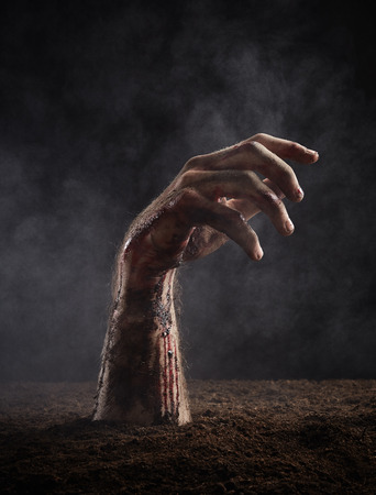 Terrible hand in blood and dirt on dark background