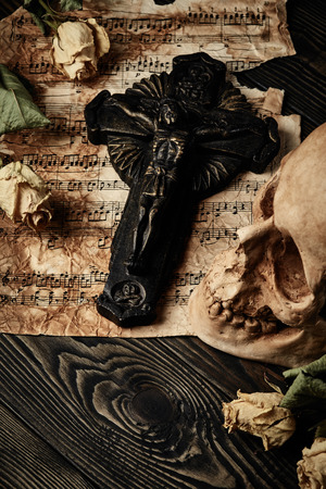 corpse flower: Vintage still life with crucifix, skull, dry roses and music notes Stock Photo