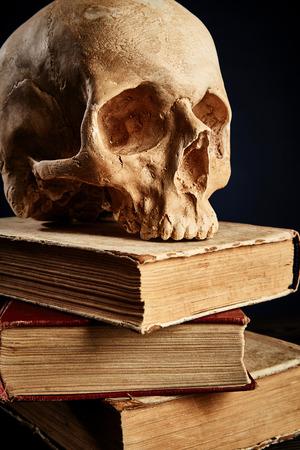 old paper background: Human skull on stack of books over black background