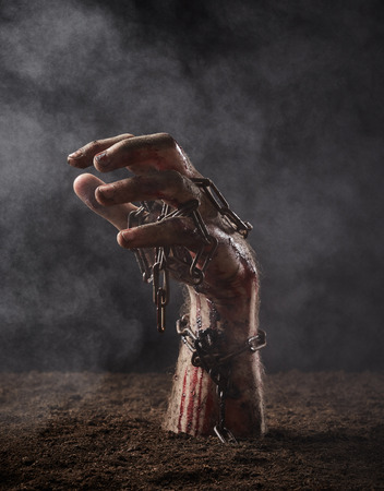 Hand of dead with chain climbs out of the ground Stock Photo