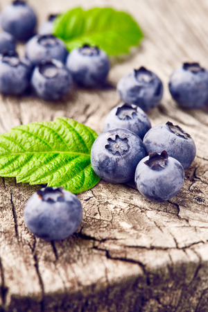 wildberry: Blueberries with green leaves on wooden background Stock Photo