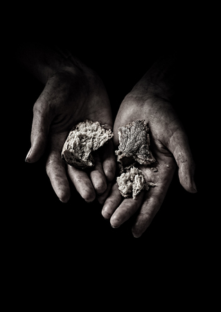 Poverty concept. Hands with dry bread