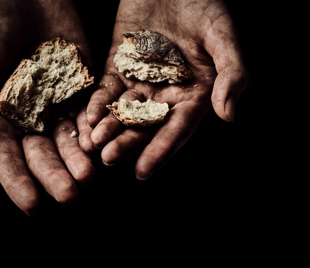 disadvantaged: Poverty concept. Hands with dry bread