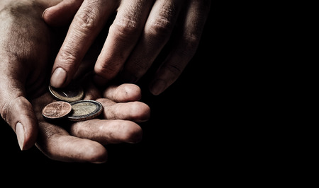 Hands of beggar with few coins on black background