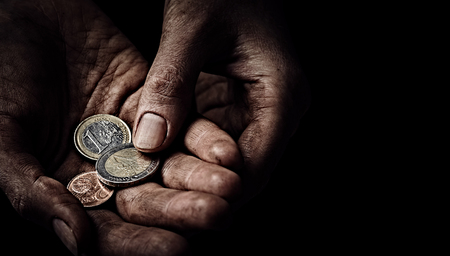 Beggar hands with few coins close up. Poverty concept Фото со стока