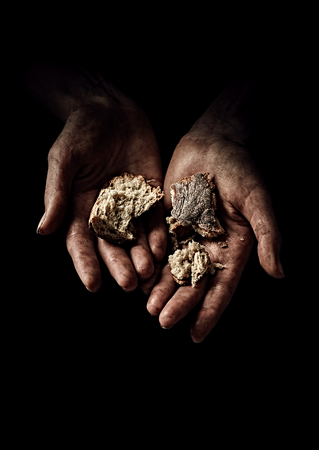 Poverty concept. Hands with rusks on black background Stock Photo