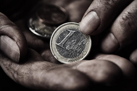 Coin in dirty hands close up. Poverty concept