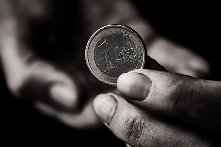 Coin in beggar hand close up. Poverty concept