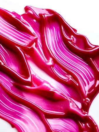 Liquid lipstick smudged over white background