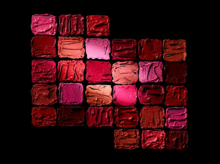 Different colors lipstick smudges isolated on black background