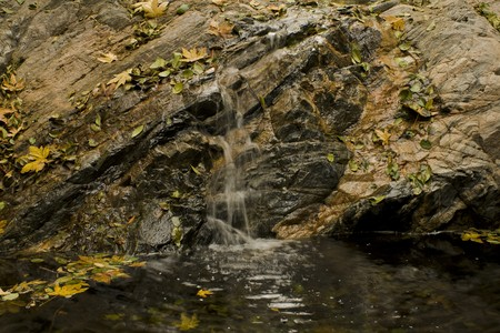 backwoods: Waterfall,rocks, and boulders in California canyon with pool at base.