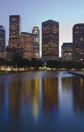 Los Angeles skyline at dusk with buildings reflected in water pool.
