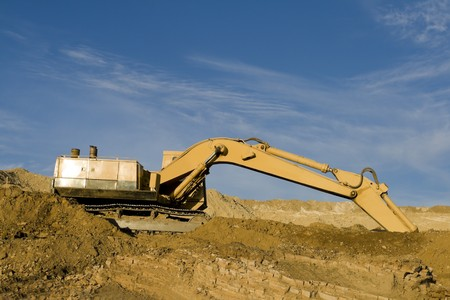 frontend: Excavator on construction site with dirt against blue sky.