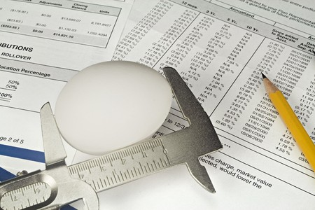 Nest Egg being measured against a background of 401K investment statements and documents. photo