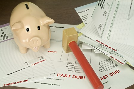 due: Pink piggy bank with toy hammer pictured against a background of past due bills and invoices.