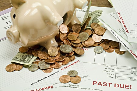 emptied: Piggy bank with emptied contents of US currency on background of overdue bill and invoices.