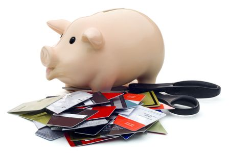 frugality: Piggy bank, scissors, cut-up credit card isolated  against white background with soft shadow