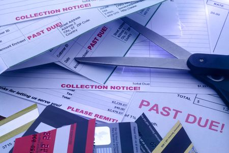 debt collection: Bill, cut up credit cards, and scissors indicating resolve to reduce expenses. Stock Photo