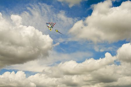 Unique Kite Flying High in Cloudscape Against Blue Sky