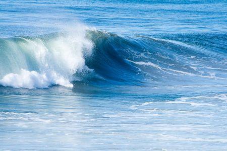 Blauwe oceaan en surf met golven op heldere, zonnige dag.