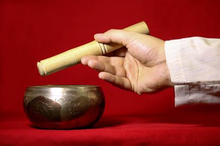 singing bells: Tibetan singing bowl on the red background.