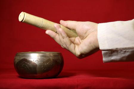 singing bowl: Ciotola tibetana di canto su sfondo rosso. Archivio Fotografico