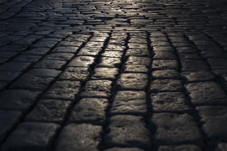 도로에서 본 빛의 반사와 블랙 자갈길 돌도 배경입니다. 검정 또는 어두운 회색 돌 포장 텍스처입니다. 돌 포장 도로에 빛