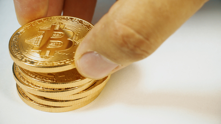 The mans hand puts the bitcoins in a column. Hand counting gold bitcoins. Crypto currency Gold Bitcoin - BTC - Bit Coin