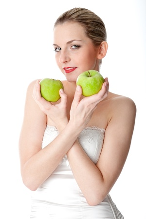 decolletage: A young, beautiful woman holding two green apples