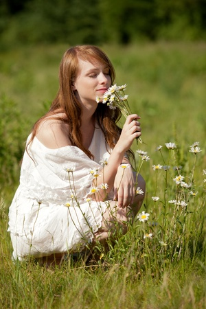 A young, beautiful lady picks flowers on a summer meadow  photo