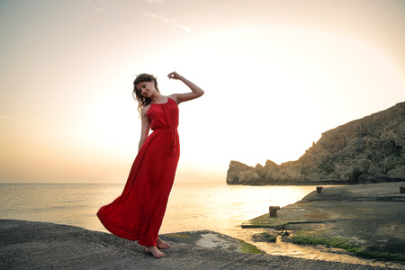 Beautiful woman dancing in front of the sea with a red dress