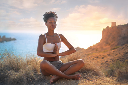 african american silhouette: Beautiful woman doing yoga in an amazing natural place Stock Photo