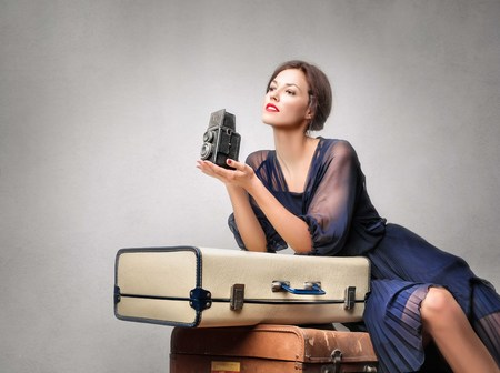 Elegant woman with old suitcases and a vintage camera