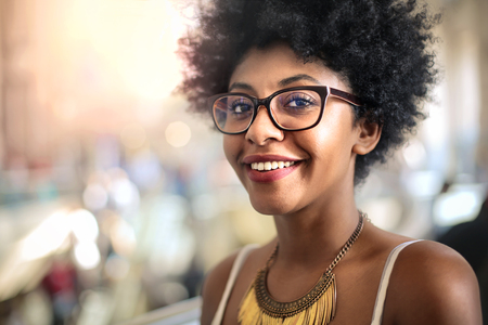 African woman in glasses is smiling