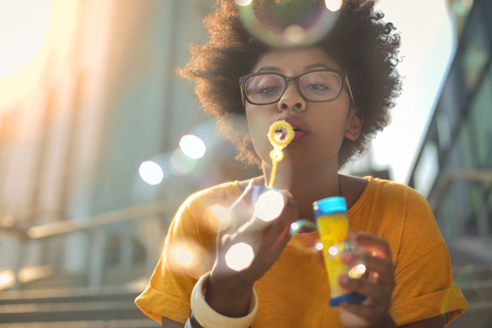 Young woman is blowing bubbles Imagens