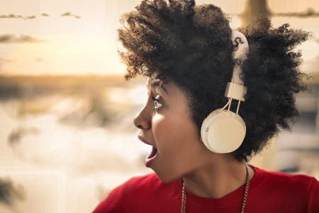 Surprised woman is listening to music Imagens