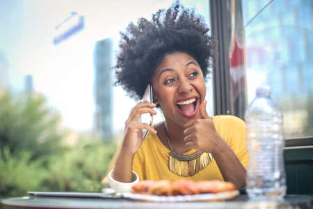 Brazilian girl is eating pizza and talking on the phone Imagens