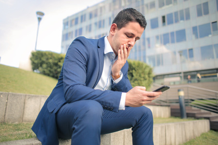 Businessman is sitting on the stairs and texting