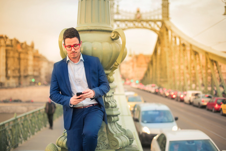 Businessman is standing on the bridge in the traffic